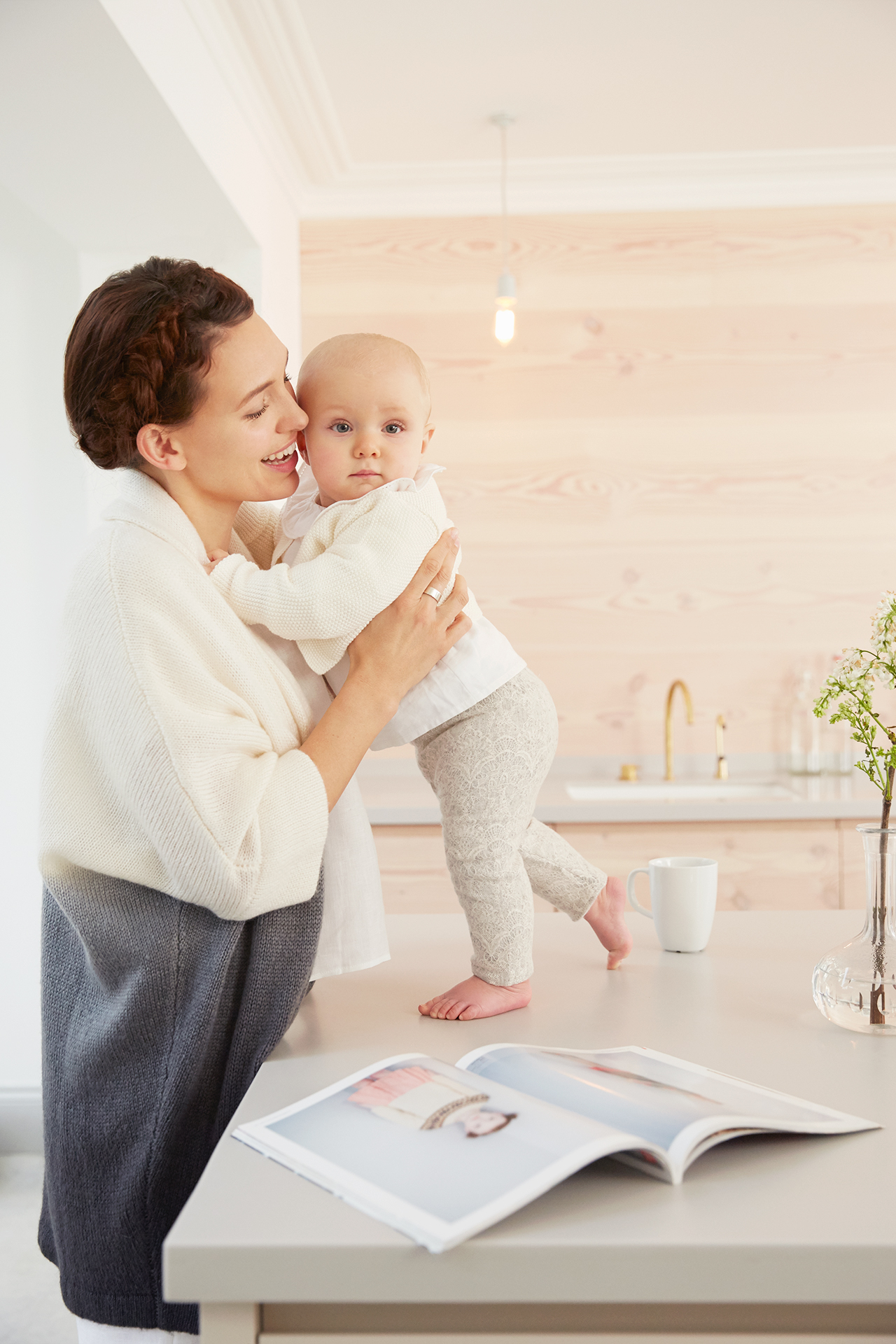 Mother with baby playing on kitchen counter