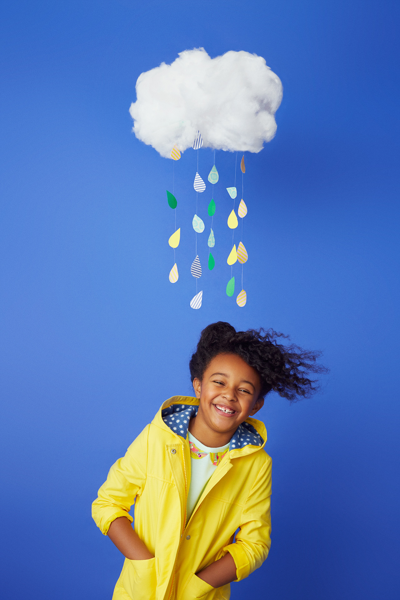 Girl laughing standing under homemade rain cloud