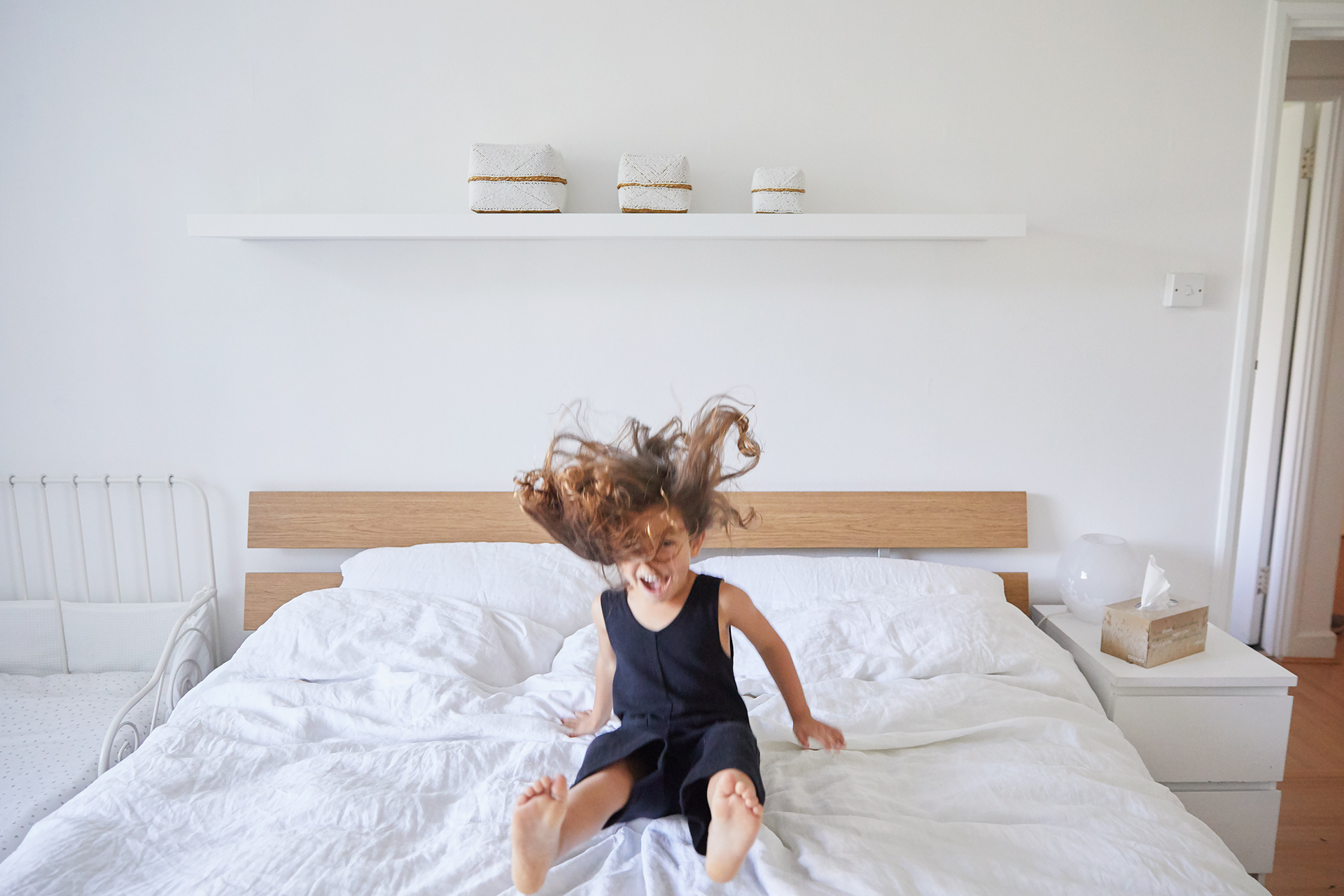 Young girl bouncing on parents bed