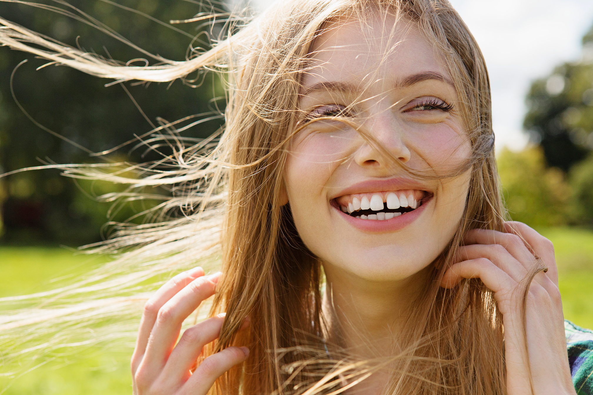 Young female laughing with wind in her hair