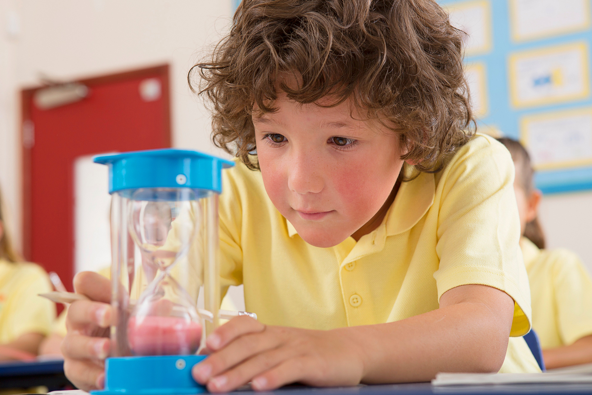 School boy looking at sand timer