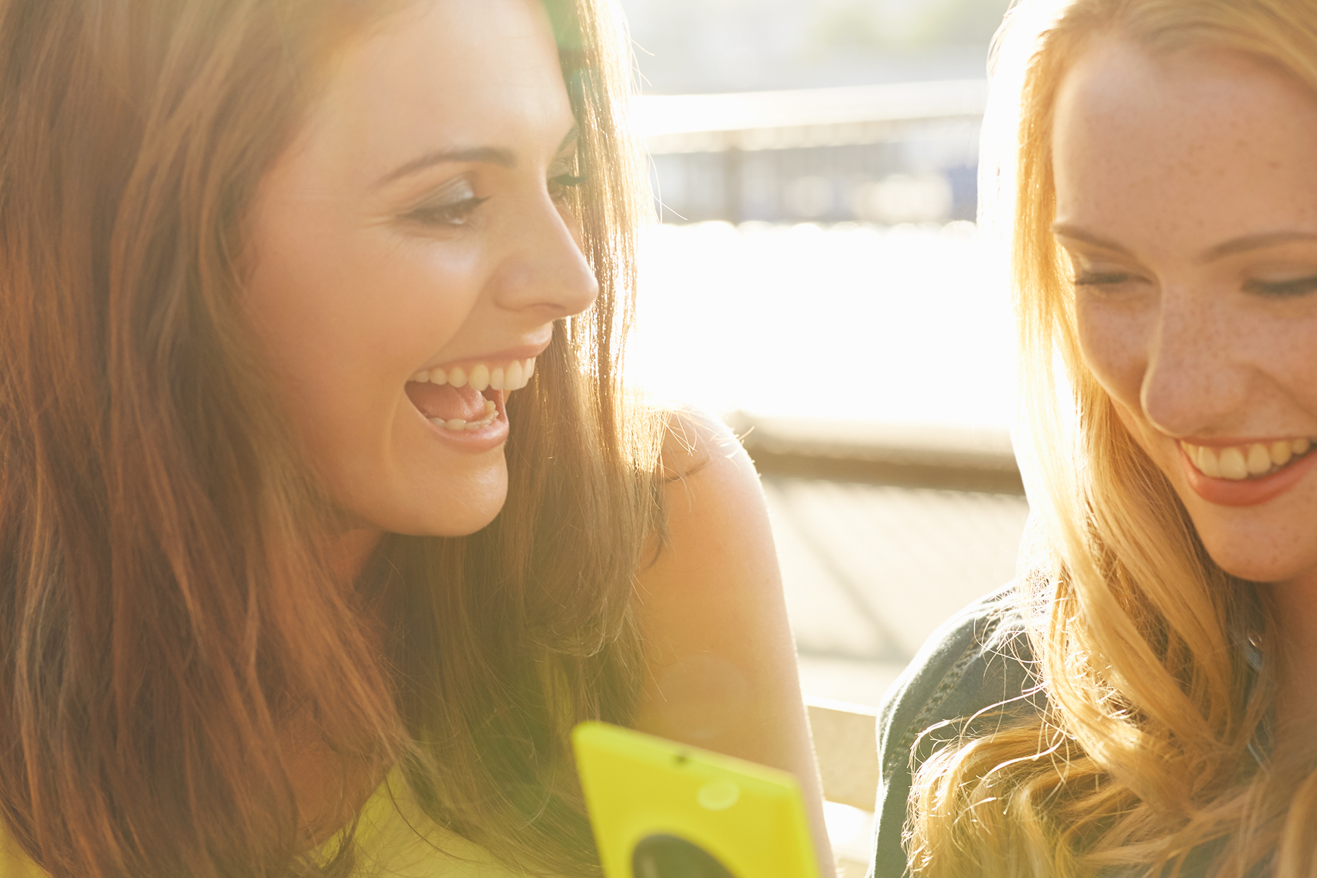 Young female friends laughing over screen on mobile phone