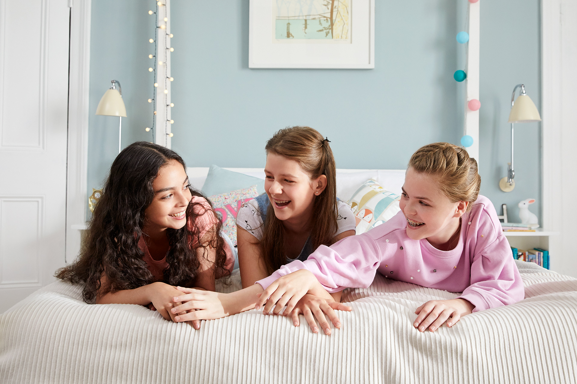 Three girl friends chatting on a bed together