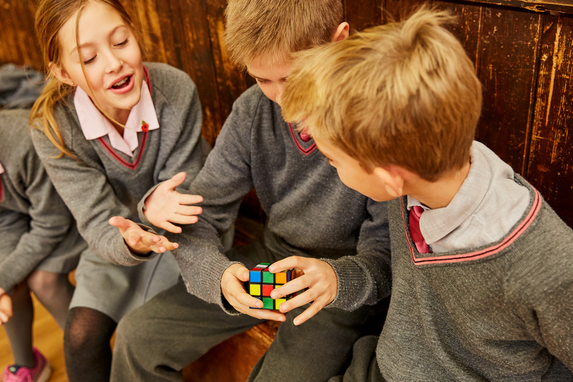 School children laughing with rubix cube