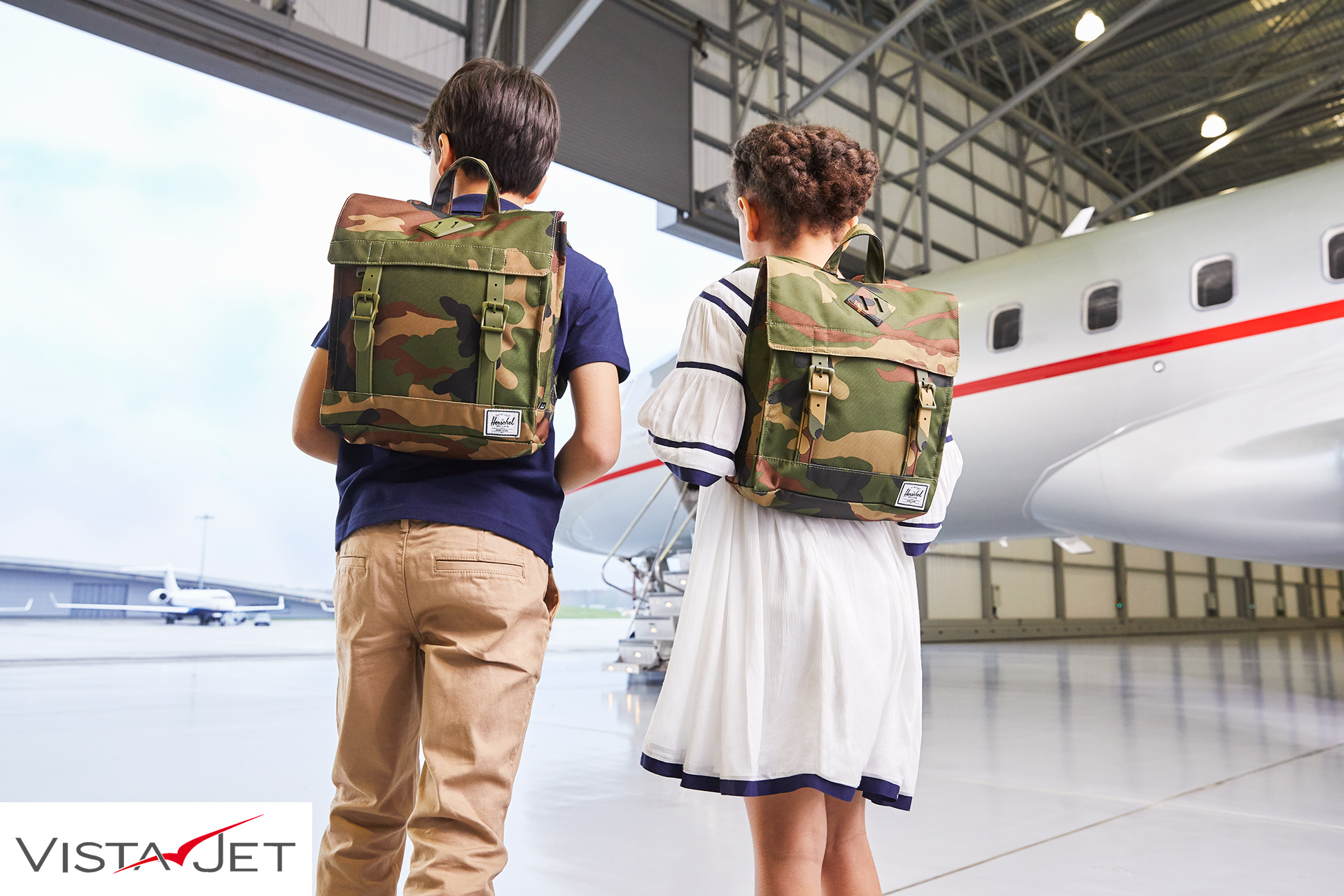 Children boarding a plane with backpacks