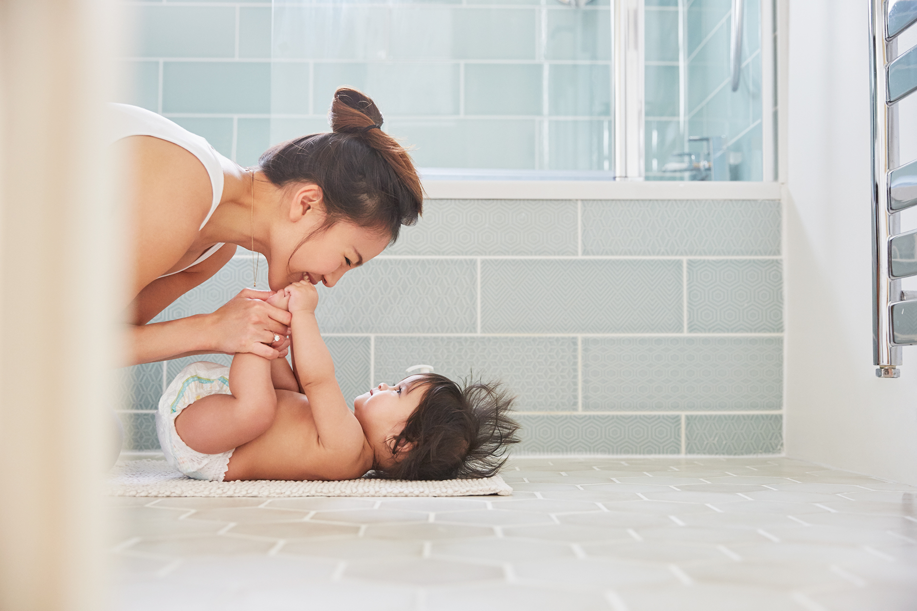 Mother with baby on bathroom floor
